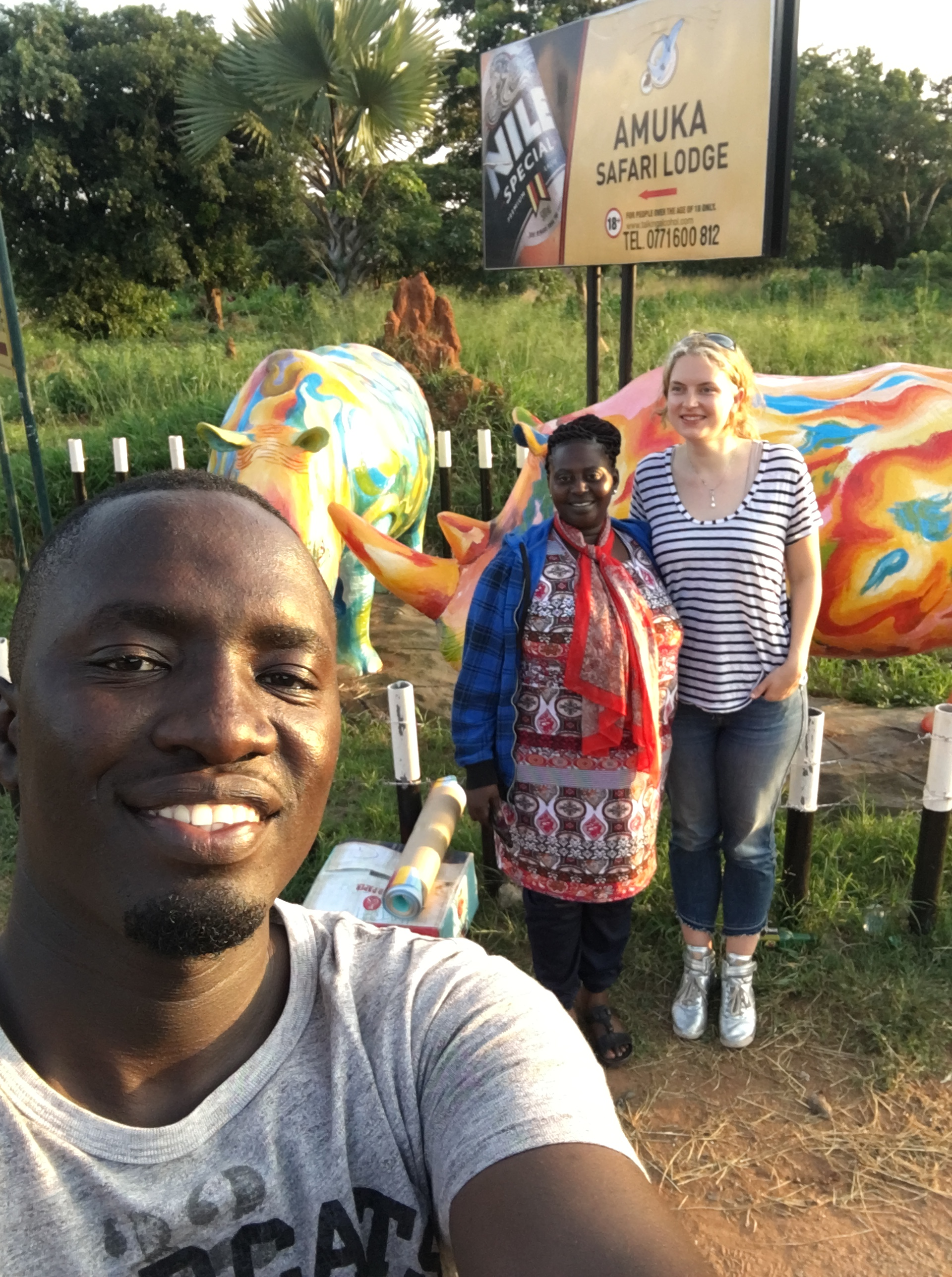 there are three people in the picture. the man in the foreground is taking the selfie. Two women are further back in the picture standing in front of a colourfully painted statue of a rhino. There is a sign behind the statue Amuka Safari Lodge