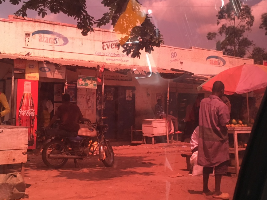 photo taken from inside a car looking out at a road side shop. on the left is a big sign with a coke bottle on it and the writing coca cola. one can see a motorbike on the left and a person walking by on the right. The picture has red tint to it due to the coloring of the car windows. Behind the shop are tropical plants