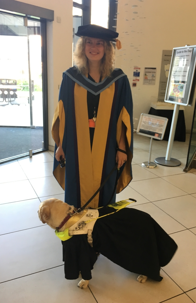 I am in a blue and yellow acadmic gown and Lassie is a black and gold graduation gown