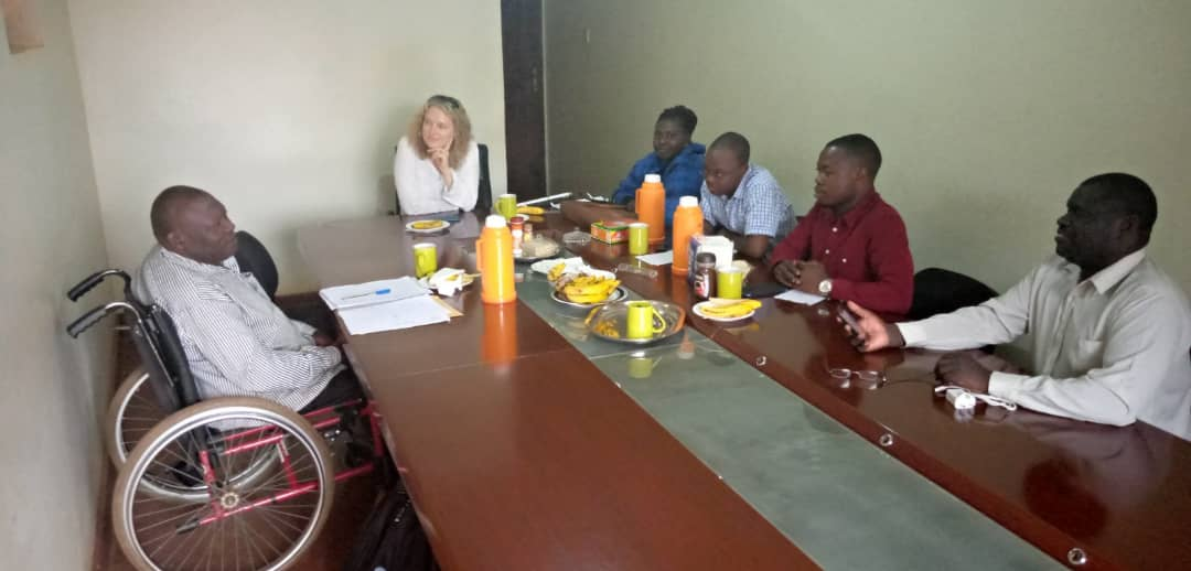 6 people sitting in a garage that doubles as a meeting room. Everyone sits around a boardroom table. There are juices, teas and fruit on the table. The person on the left is sitting in a wheelchair