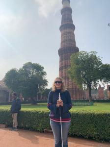 I am holding a 3D-printed model of the Qutub MInar while standing in front of the real Minar. The Minar is a high tower (minerette) in three sections that get thinner the higher up they are.