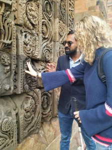 My guide and I are standing in front of wall with lots of carvings. I am exploring the carvings with my right hand while holding my cane with my left