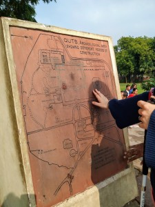An upright brown tactile map of  Qutub MInar. my right hand is exploring one of the lines on the map.